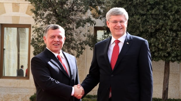 Jordan King Abdullah II, left, shakes hands with Canadian Prime Minister Stephen Harper, right, at the royal palace in Amman on Thursday. Harper pledged $105 million in development assistance for Jordan.