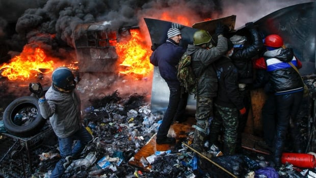 A protester throws stones towards riot police as others take cover in Kyiv.