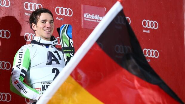 Felix Neureuther of Germany smiles on the podium after winning the slalom on the classic Hahnenkamm event in heavy snow on Friday.