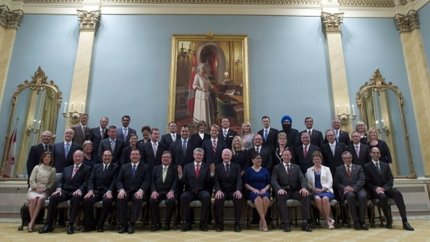 Prime Minister Harper and his cabinet pose after their swearing in ceremony at Rideau Hall in July of last year. Rules around ministerial responsibility have changed. Now ministers don't have to take the blame for mistakes their politcal staff and bureaucrats make but they are responsible for meting out punishments.
