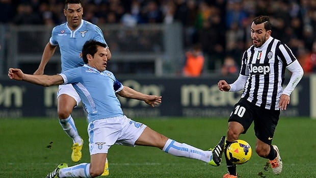 Juventus' Carlos Tevez, right, vies for the ball with Lazio's Anderson Hernanes during the match on January 25, 2014 at the Olympic stadium in Rome.