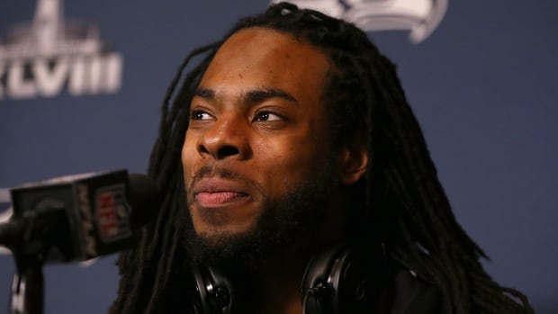 Seahawks cornerback Richard Sherman smiled and laughed while addressing reporters on Sunday in Jersey City, N.J. He didn't give the Broncos any billboard material for Sunday's Super Bowl following his post-game rant about Michael Crabtree immediately after Seattle won the NFC title last weekend.