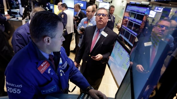 Jason Hardzewicz, left, works at his post on the floor of the New York Stock Exchange, on Monday.
