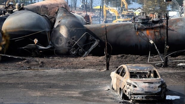 A burnt out vehicle sits near the wreckage of a train car following a train derailment in Lac Megantic, Que.