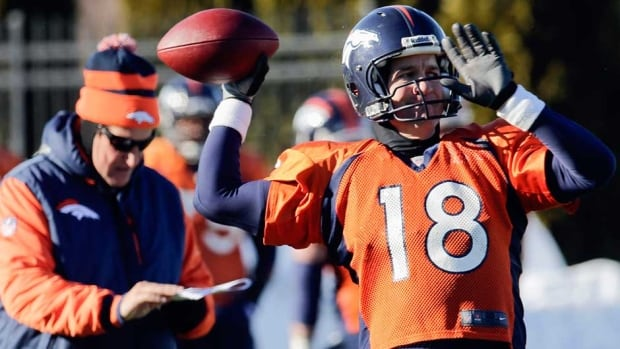 Denver Broncos offensive co-ordinator Adam Gase, left, checks his clipboard as quarterback Peyton Manning (18) throws a pass during their practice session for the Super Bowl at the New York Jets Training Center in Florham Park, N.J. on Wednesday.