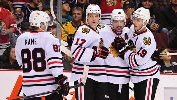Chicago Blackhawks forward Jonathan Toews (19) and defenseman Johnny Oduya (27) and forward Patrick Kane (88) congratulate forward Patrick Sharp (10) after scoring against the Vancouver Canucks on Thursday.