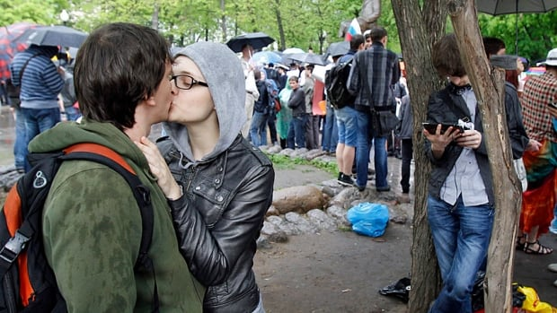 A couple share a kiss during an opposition protest in central Moscow in May 2012. Russia's young people have been protesting, counter-protesting and leaving the country in significant numbers to find work.
