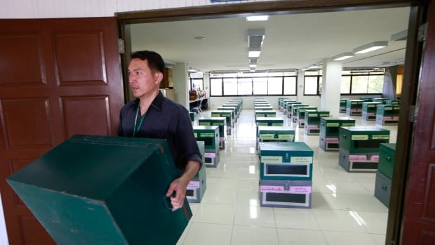 A Laksi district official carries a ballot box on Friday after anti-government protesters blocked his office where the ballot boxes are kept in Bangkok. Thailand's general election is scheduled for Sunday, Feb. 2 but the main opposition Democrat Party is boycotting it.