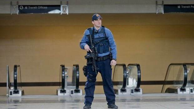A New Jersey Transit Police sergeant stands watch in the main hall at the Secaucus Junction Station Secaucus, N.J., as part of the extra security for Sunday's Super Bowl. The FBI and other law enforcement are investigating white powder that was mailed to businesses near the site of Sunday's Super Bowl.