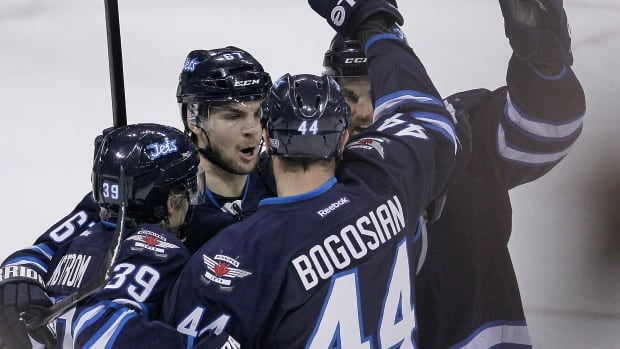 The Winnipeg Jets' Tobias Enstrom (39), Michael Frolik (67), Zach Bogosian (44) and Andrew Ladd (16) celebrate Bogosian's goal against the Vancouver Canucks during the first period Friday night at the MTS Centre.