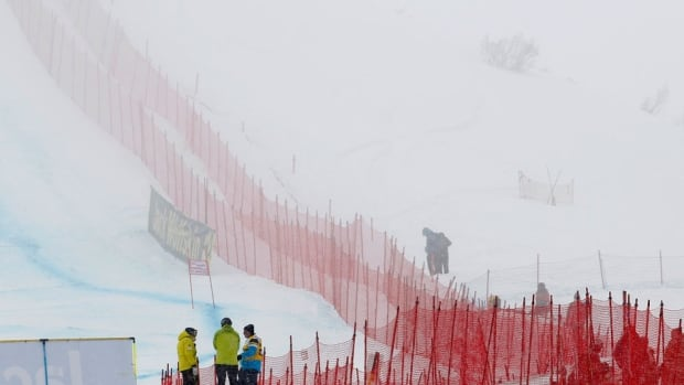 Race officials stand on the track during a weather delay at the men's World Cup downhill race in St. Moritz, Switzerland on Saturday. The race was cancelled due to fog.