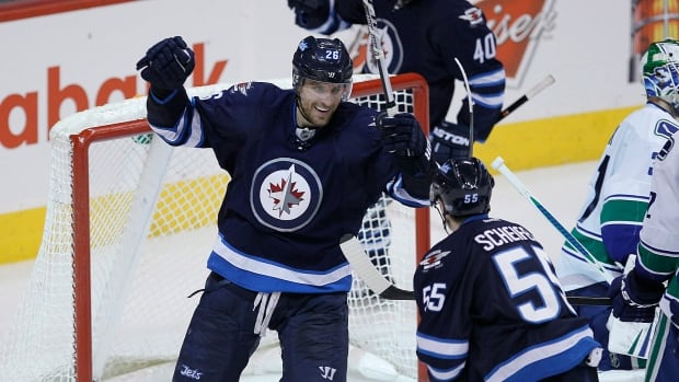 Winnipeg Jets' Blake Wheeler (26), Devin Setoguchi (40) and Mark Scheifele (55) celebrate Setoguchi's game winning goal against the Vancouver Canucks during third period NHL action in Winnipeg on Friday, January 31, 2014. THE CANADIAN PRESS/John Woods