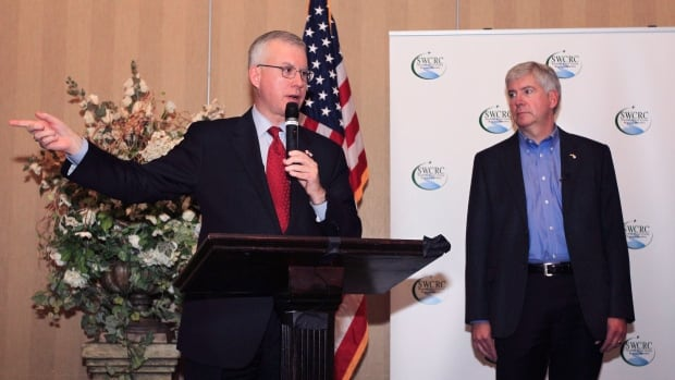 Roy Norton, seen at left standing with Michigan Gov. Rick Snyder in an Oct. 15, 2012, photo, has told the Detroit Free Press that the Canadian government will begin purchasing land in Detroit for the U.S. portion of a new bridge that will link the two nations.