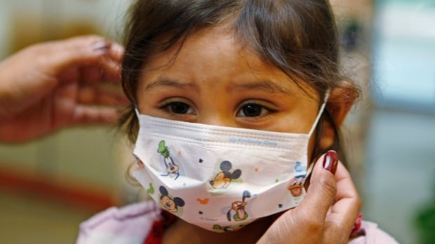 Sheila Garcia, 3, has a mask put on her head before visiting a patient at the hospital in Palo Alto, Calif. The Canadian Lung Association said most children under the age of three will contract RSV and it's usually a mild illness that will go away on its own.