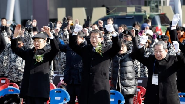 South Korean Unification Minister Ryoo Kihl-jae, centre, celebrates with North Korean defectors, refugees and their family members near a South Korean border village. The divided Koreas will meet to arrange reunions for families separated by the 1950-53 Korean War.