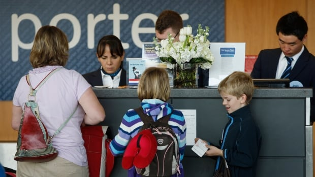 Porter Airline ticket agents check in a family at Dulles International Airport in Virginia. The airline has been ordered to revise its rules on compensating passengers who are bumped from their flights.