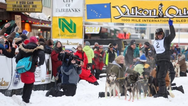 Brent Sass of Eureka, Alaska, waves to the crowd as he gets ready to leave the starting line of the Yukon Quest International Sled Dog Race on Saturday in downtown Fairbanks, Alaska. Sass was first into the checkpoint in Eagle, Alaska, on Tuesday.