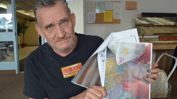 James Yanke holds up a photo of bedbugs he says were in an apartment at Spence Court in Thunder Bay. Yanke has been collecting documents and photos of the infestation since it began in 2009.