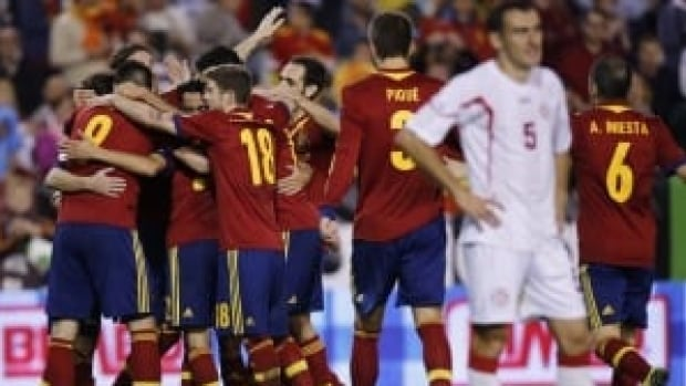 In this Oct. 15 file photo, Spain's players celebrate after Juan Mata, obscured, scored against Georgia to secure a spot in 2014 World Cup.
