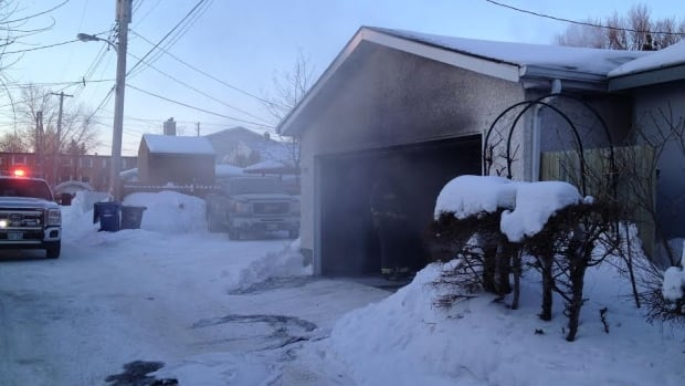 Smoke drifts out from a garage fire on Beaverbrook Street in Winnipeg's River Heights neighbourhood on Thursday.
