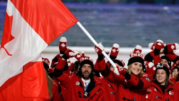 Hayley Wickenheiser carries the Canadian flag as she leads the team during the opening ceremony of the 2014 Winter Olympics in Sochi, Russia, Friday.