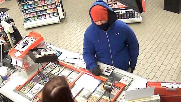 The suspect, wearing a blue hoodie and orange hat, fled with an undisclosed amount of money.