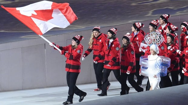 Canada's flag bearer, ice hockey player Hayley Wickenheiser  leads her delegation during the Opening Ceremony of the Sochi Winter Olympics at the Fisht Olympic Stadium on February 7, 2014 in Sochi.