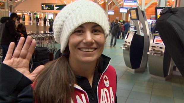 2010 snowboard cross Olympic gold medalist Maelle Ricker of West Vancouver waves goodbye from the Vancouver airport Saturday afternoon as she heads for Sochi.