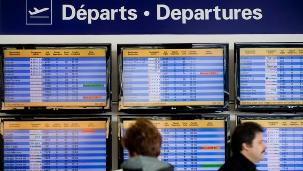 Passengers stand next to a departures board at Trudeau Airport in Montreal. Allegations about rude, unhelpful staff and poor communication at airports across Canada were among some of the complaints passengers made to the Canadian Transportation Agency last year.