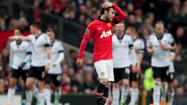 Manchester United's Juan Mata looks on as Fulham players celebrate their first goal at Old Trafford Stadium, Manchester, England, Sunday Feb. 9, 2014.