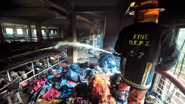 In this photo taken Nov. 25, 2012, a firefighter douses the interior of the burned out Tazreen garment factory in Savar, on the outskirts of Dhaka, Bangladesh. The factory fire killed 112 garment workers.