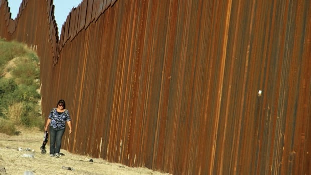 A woman walks past the border fence between Mexico and the U.S. near the Arizona border of Nogales, where a 2010 shooting resulted in the death of a U.S. border agent. A man was sentenced Monday to 30 years in the slaying.