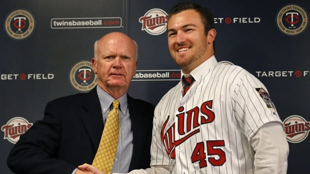 Minnesota Twins GM Terry Ryan, left,  is seen shaking hands with newly signed starting pitcher Phil Hughes on Dec. 5, 2013.