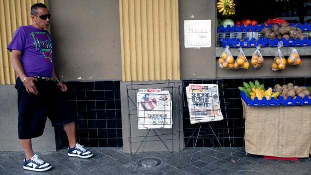 A man in Ponce, on Puerto Rico's southern coast, stands next to a stand displaying newspapers with headlines referring to last week's downgrade by Standard & Poor of the U.S. territory's credit rating. Standard & Poor's, Moody's and Fitch have now all downgraded Puerto Rico's debt to junk status in the latest blow to an economy that has been battling chronic recession, high unemployment, population decline and a perennial budget shortfalls that have left it with $70 billion in debt.