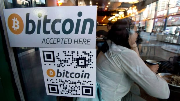A Bitcoin ATM sticker is posted to the window of a coffee shop in Vancouver, Monday, Oct. 28, 2013. Will that be cash, credit card or Bitcoin? A small number of Canadian businesses now accept Bitcoin, the digital currency that made its debut five years ago, and has been gaining momentum ever since.