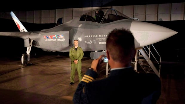 A Canadian Forces pilot poses in front of an F-35 fighter prior to an announcement in Ottawa in July 2010. In its 2014 budget, the government moved to reclaim $3.1 billion in military procurement funds it says the military can't spend.