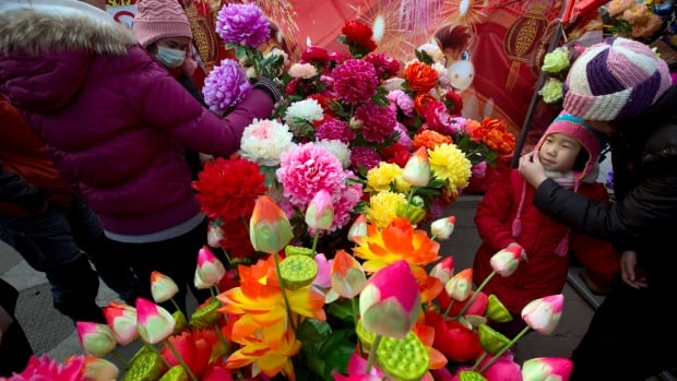 Visitors buy plastic flowers at a spring festival temple fair held at the Dragon Lake park in Beijing, China on Feb. 5, 2014. China reports its imports climbed by 10 per cent and exports were up 10.6 per cent in January.