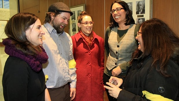 Members of the Hamilton Sanctuary City Coalition, donning yellow armbands, celebrate outside council chambers on Wednesday. From left: Josee Oliphant, Blake McCall, Ani Chenier, Caitlin Craven and Maria Antelo. The city voted unanimously not to quiz immigrants who access city services on their citizenship status.