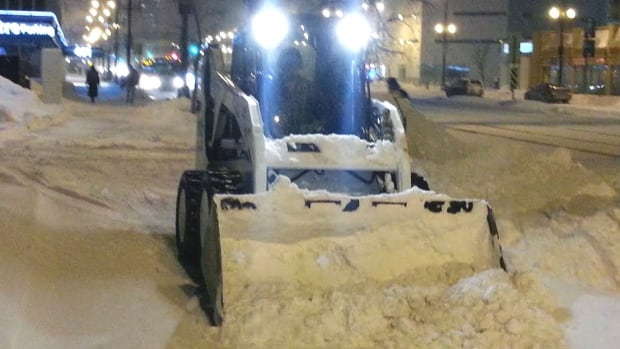 A Bobcat clears snow at the University of Winnipeg campus in downtown on Thursday morning.