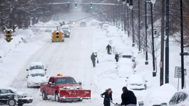 People dig out vehicles after overnight snow on Friday in Albany, N.Y. Schools were closed across a swath of eastern New York from the mid-Hudson Valley to the Albany area.