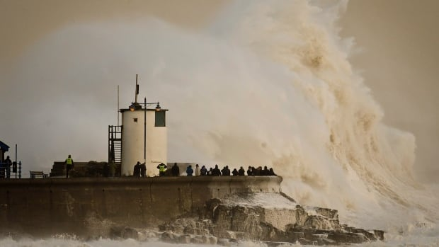 Waves break over Porthcawl harbour, south Wales, as the region continues to be battered by high winds and heavy rain.