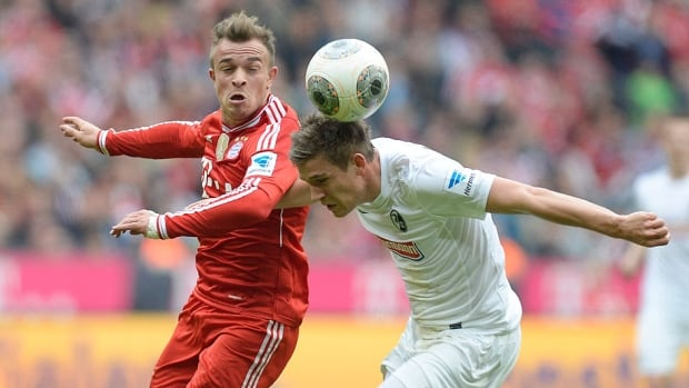 Bayern Munich's Swiss midfielder Xherdan Shaqiri, left, and Freiburg's defender Oliver Sorg vie for the ball during the German first division Bundesliga match on Saturday in Munich, Germany. Shaqiri will miss Wednesday's Champions League round of 16 match League versus Arsenal after tearing a muscle at the back of his right thigh in the second half.