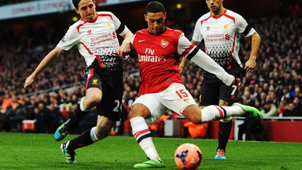 Alex Oxlade-Chamberlain, right, of Arsenal tries to get his cross in ahead of Joe Allen, left, of Liverpool during the FA Cup fifth-round match Sunday in London.