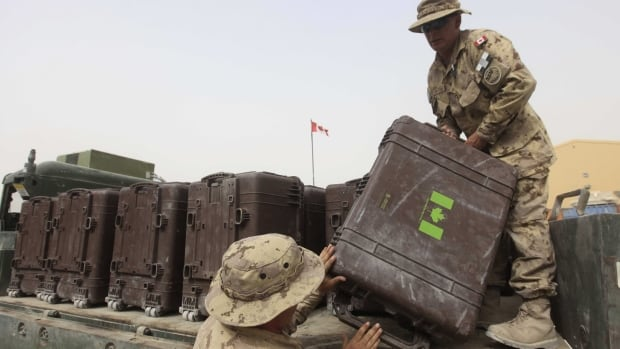 Canadians soldiers load baggage on the back of a truck at Kandahar airbase in Afghanistan, Saturday, July 16, 2011. Hundreds of containers of military gear were stranded in Kandahar following the end of the Canadian combat mission there.