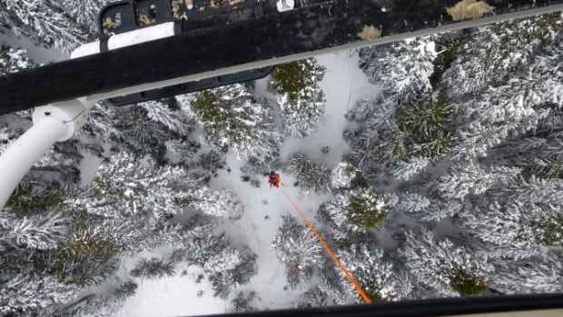 View from the helicopter window as a skier is lifted by long line from Needle Peak, the site of an avalanche near the Coquihalla Saturday afternoon