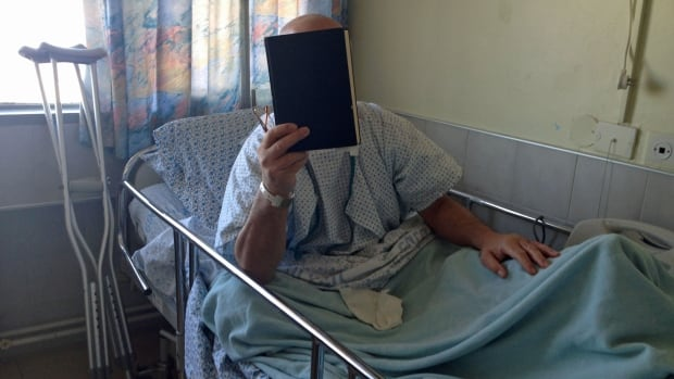 """Nasser,"" a Syrian patient, was brought to Ziv Hospital in the northern Israeli community of Safad last September for treatment he couldn't get at home after being involved in a car accident near the Syrian city of Dera'a. He is hiding his face because he is fearful of being mistreated when he returns to Syria for having been inside Israel."