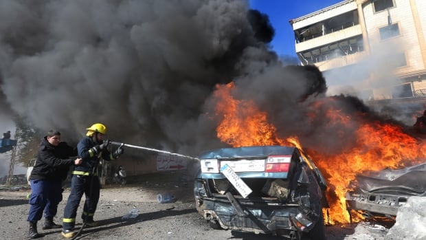 Lebanese firefighters extinguish a burned car at the site of an explosion in a Beirut, Lebanon suburb on Wednesday.. A blast in a Shia district in southern Beirut killed several people.