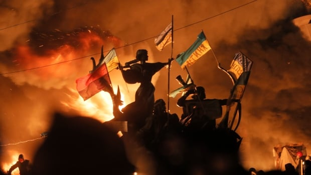 Monuments to Kiev's founders burn as anti-government protesters clash with riot police in Kiev's Independence Square on Tuesday. Ukraine's Olympic Committee says the IOC has rejected a request for its athletes at the Sochi Games to wear black armbands honouring those who died in the protests.
