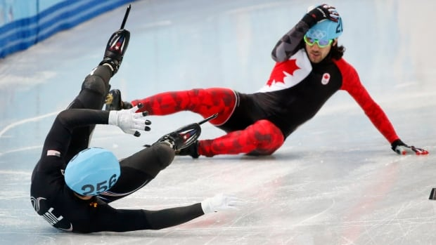 Canada's Charles Hamelin (R) and Eduardo Alvarez of the U.S. fall during the men's 1,000 metres short track speed skating quarter-finals.
