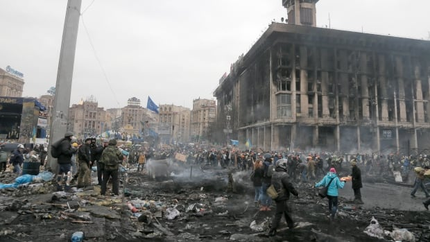 People pass through Independence Square, the epicenter of the country's current unrest, Kiev, Ukraine, Thursday, Feb. 20, 2014. Fierce clashes between police and protesters, some including gunfire, shattered a brief truce in Ukraine's besieged capital Thursday, killing numerous people. The deaths came in a new eruption of violence just hours after the country's embattled president and the opposition leaders demanding his resignation called for a truce and negotiations to try to resolve Ukraine's political crisis.(AP Photo/Efrem Lukatsky)